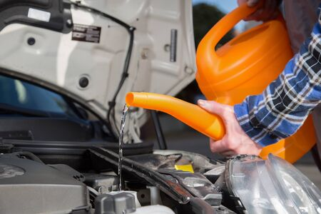 A man fills his car with fresh water with a orange canister.