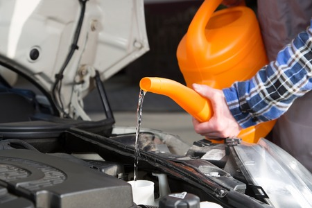 With the help of a watering can a mechanic fills water in the engine tank.