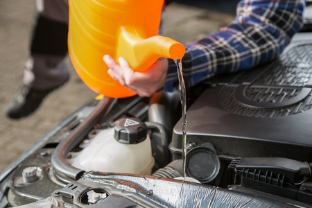 A man is filling the car water cooling system with fresh water from an orange canister.