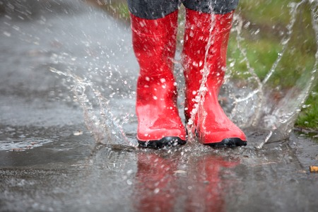 A pair of red rubber boots are jumping into a big puddle.の写真素材