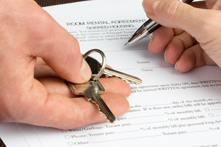 Photo pour A woman is filling out a room rental agreement document with a key and pen in her hand. - image libre de droit