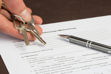 Photo pour A german rental agreement with house keys in one hand. A pen is lying on the document. - image libre de droit