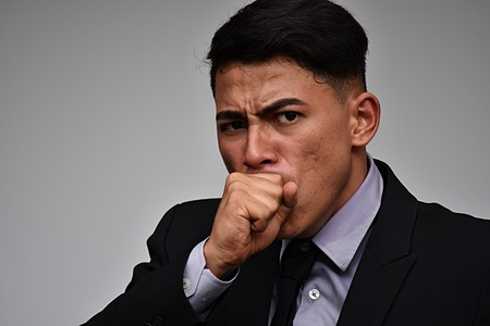 Young Colombian Business Man Coughing Wearing Business Suit