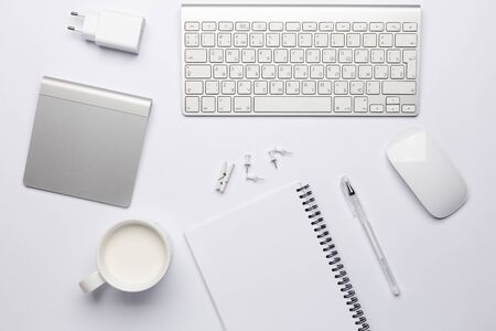 Photo for Empty white notebook with pen, working place with keyboard and touchpad. Free white space for notes and text. - Royalty Free Image
