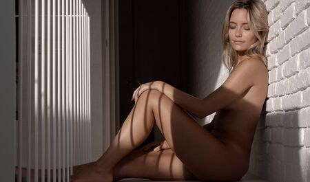 Foto de beautiful naked woman seated agaisnt a wall posing in lovely late afternoon light - Imagen libre de derechos