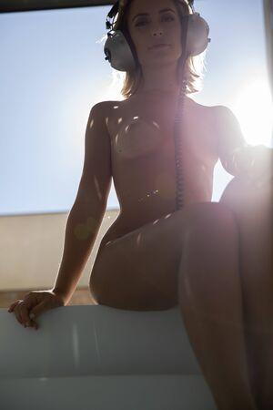Foto de beautiful naked woman seated with headphones, backlit agaisnt the afternoon sun - Imagen libre de derechos