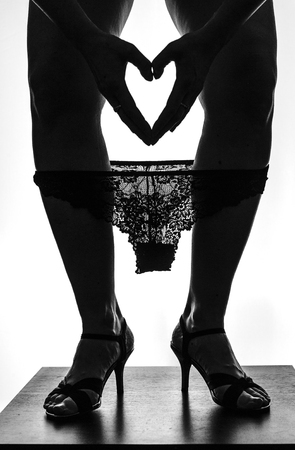 Silhouette of beautiful young woman legs on high heels with laced pinties and heart from hands