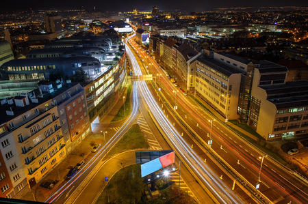 Dynamic city life in dark night. Prague from beauty bird perspective. Cityscape to highway full of car lights