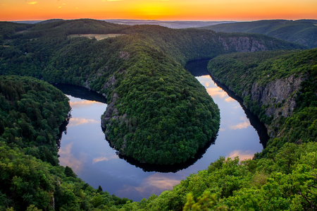 Beautiful sunset landscape view to Czech Republic river Vltava, close to Prague. Orange sky during summer with clouds reflection in the water.