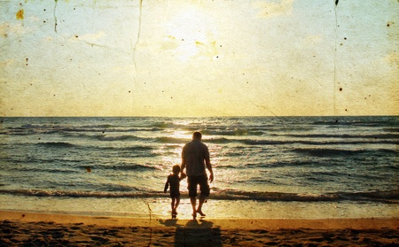 Father and son at sea watching the sunset. Photo in old image style.