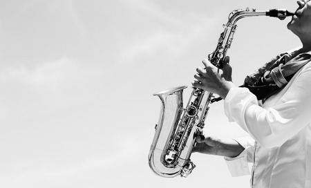 Saxophonist playing on saxophone on blue sky background