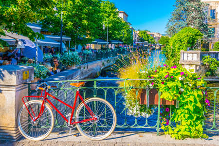 L'ISLE-SUR-LA-SORGUE, FRANCE, JUNE 24, 2017: Bicycle locked to a railing in the historical center of l'Isle sur la Sorgue in France