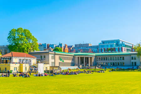 Students are having a picnic on a field inside of the trinity college in Dublin, Ireland