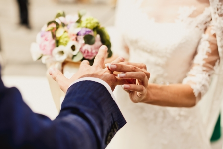 Close up of holding hands with wedding rings