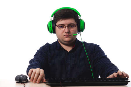 Photo pour Young guy in a dark blue shirt green headphones gamer in glasses for vision on a white background. isolate. copy space - image libre de droit