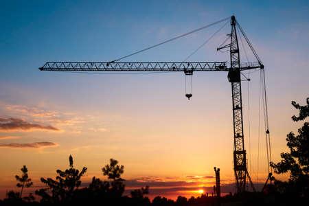 Photo pour silhouette tower construction crane on sunset background, copy - image libre de droit