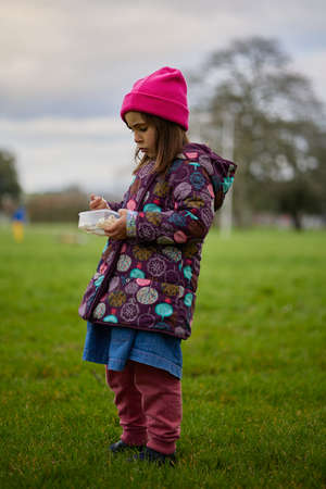 Foto per Caucasian girl eating popcorn standing up. With casual clothes and a pink hat. In a natural park. - Immagine Royalty Free
