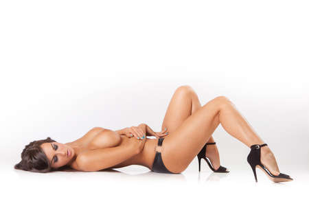 Photo for glamour attractive brunette girl with big breasts lying on white floor - Royalty Free Image