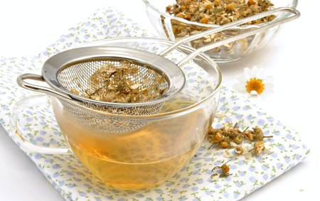 Cup of chamomile tea with strainer over a bowl at the back another glass of chamomile blur