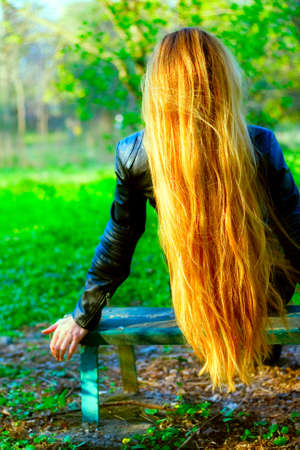 Back of woman with beautiful blond hair on bench park