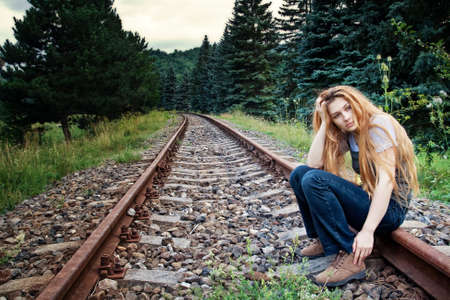 Sad suicidal lonely young woman on railway track