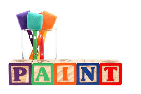 Glass of colorful paint sponges behind the word &quot,paint&quot, spelt with alphabet blocks