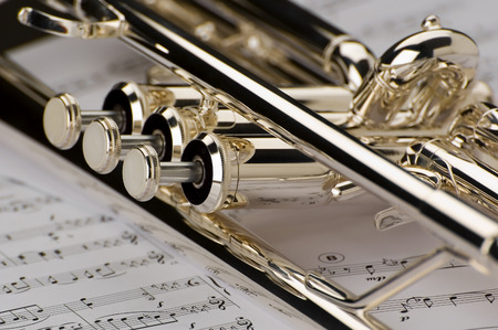 Trumpet on musical notes as background close up