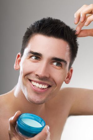 Young handsome man applying hair gel close up