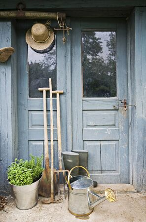 Gardening tools infront of old house doors