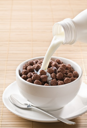 Milk pouring on chocolate cereal balls close up