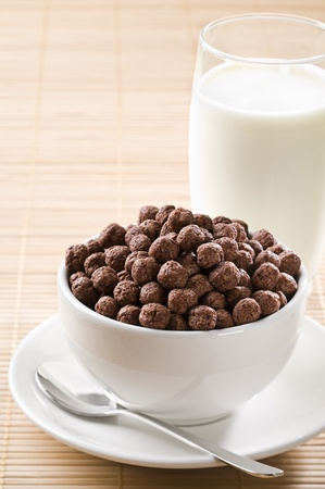 Milk with chocolate cereal balls close up