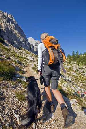 Young woman with dog on a sunny day hiking in high mountains