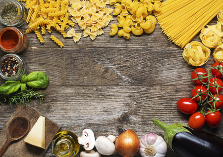 Raw Pasta with ingredients on wooden background