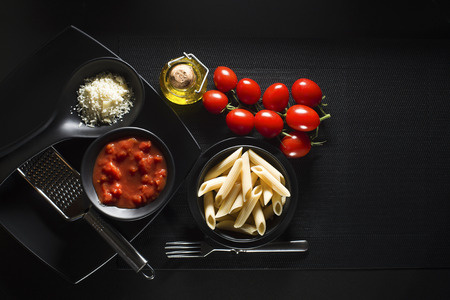 Penne pasta with tomatoes sauce and parmesan on black background