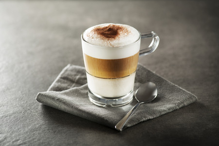 Glass of hot Latte macchiato coffee close up.