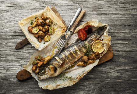 Foto de Baked sea bass with roasted potatoes on wooden table - Imagen libre de derechos