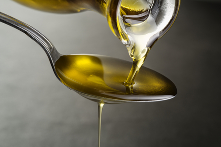 Photo pour Oil pouring and dripping to the spoon close up - image libre de droit