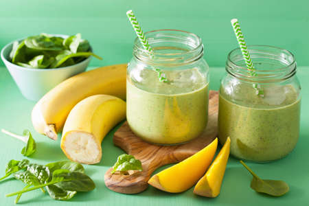 healthy green smoothie with spinach mango banana in glass jarsの写真素材
