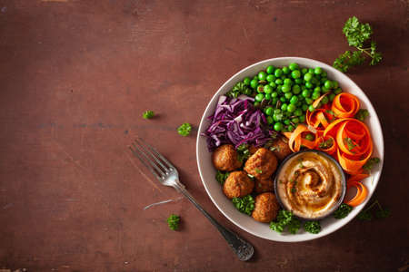Photo for healthy vegan lunch bowl with falafel hummus carrot ribbons cabbage and peas - Royalty Free Image