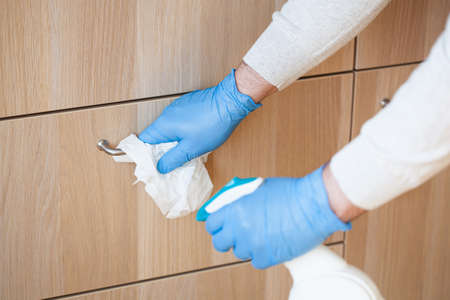 Foto de man hands in gloves disinfecting chest of drawers handle, killing virus on surface - Imagen libre de derechos