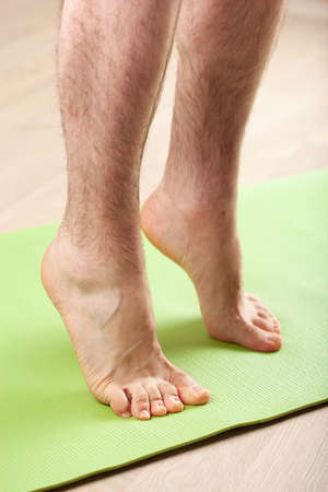 Photo pour man doing flatfoot correction gymnastic exercise standing on toes at home - image libre de droit