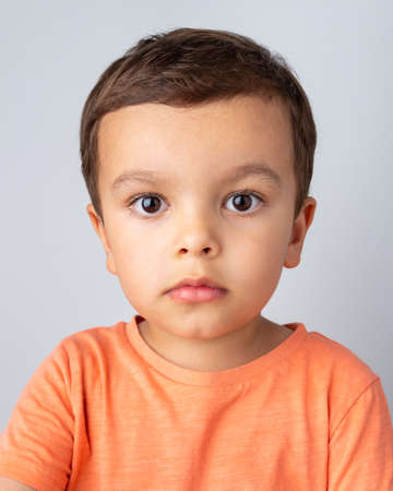 Photo for Cute three year old boy portrait, toddler wearing orange tee shirt and shot against a light grey background. - Royalty Free Image