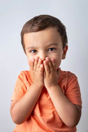 Photo for Cute three year old boy portrait, toddler covering his mouth with both hands. - Royalty Free Image
