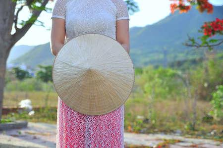 Foto de Vietnamese long dress with traditional leaf hat - Imagen libre de derechos