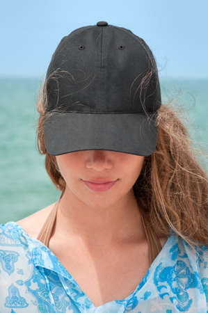 Girl with black baseball cap and curly hair