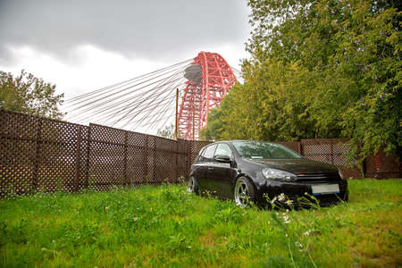 Moscow. Summer 2018. Black tuned Volkswagen Golf with chrome wide wheels against the backdrop of a picturesque bridge. Standing on the grass
