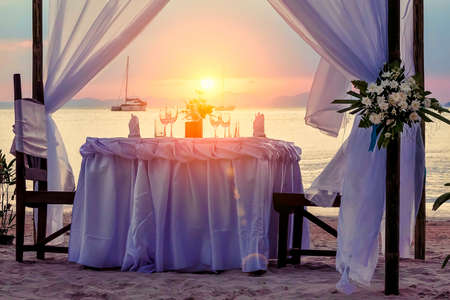 Foto de Decorated for a romantic dinner table on the sandy beach. Against the backdrop of sunset, yachts and mountains. - Imagen libre de derechos