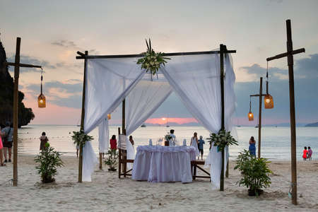 Photo pour Tourists enjoy the sunset view on the beach. On the sand set table decorated for a romantic dinner. Against the background of the cliff and the sea. - image libre de droit