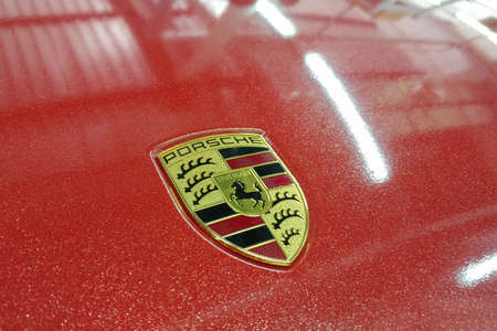 Photo for Moscow, Russia - April 14, 2019: Porsche Macan wrapped in bright red metallic color vinyl film. Logo on the hood closeup - Royalty Free Image