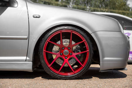Photo for red candy colored light alloy wheels on silver hatchback - Royalty Free Image